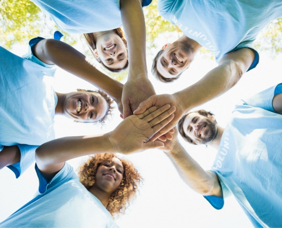 578x467 volunteers hands shutterstock_573855649