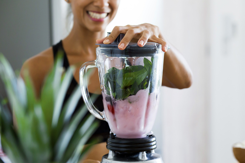 Smiling woman making a smoothie in a blender