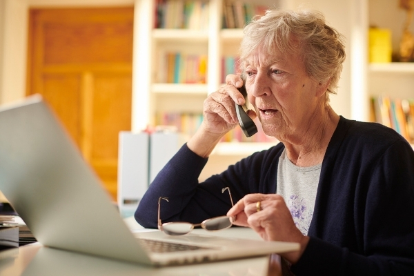 Elderly lady on the phone looking at her laptop