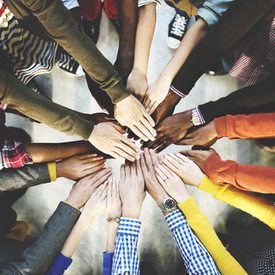 Diverse people putting hands in circle