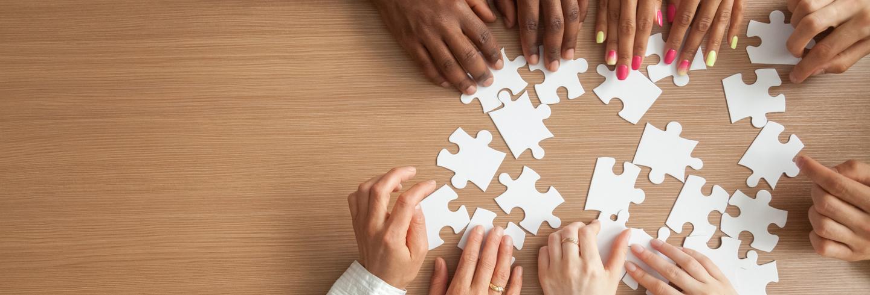 Hands solving jigsaw