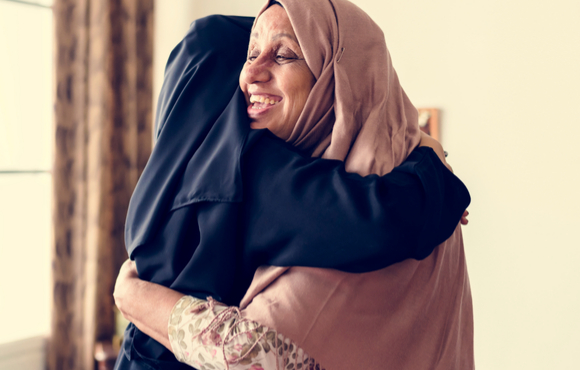 happy muslim women hugging each other on Eid