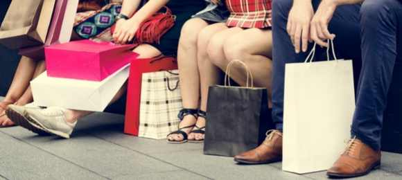 Shoppers sitting down next to bags