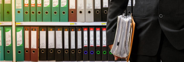 Suited man standing in front of organised folders - procedural leader