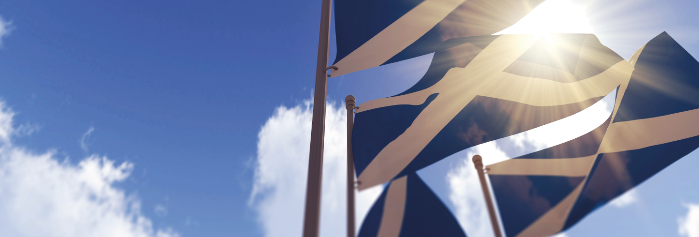 Scotland flags on flagpoles against a sunny sky
