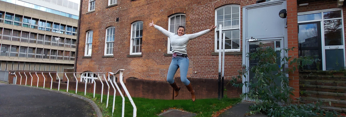 Jumping for joy outside of newly purchased building
