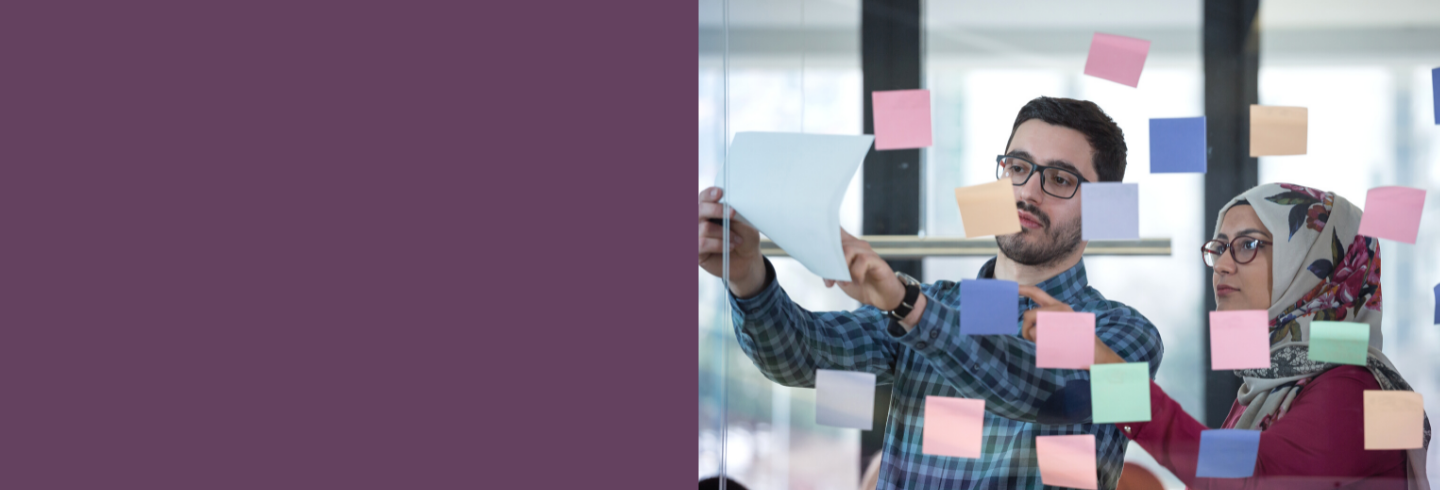Two team members standing at glass office wall with coloured sticky notes
