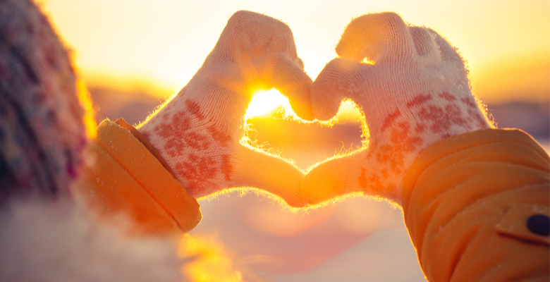 Gloves in heart shape with sunrise