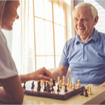 Older man and young woman playing chess