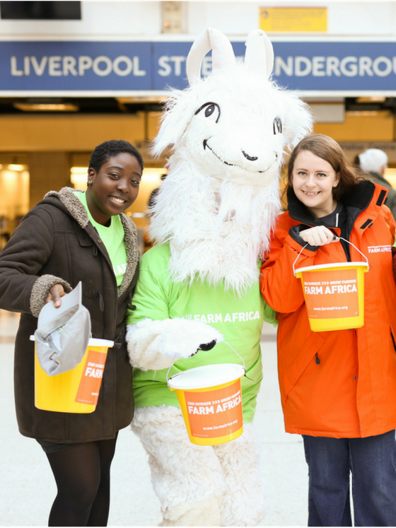 Volunteers and goat mascot bucket fundraising at underground station