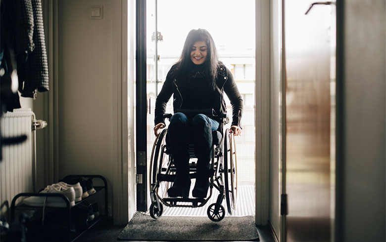 Girl in wheelchair entering through open door