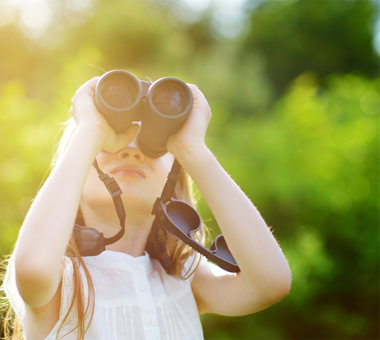 girl with binoculars looking in distance