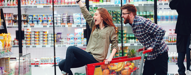 Happy people having fun while choosing food in the supermarket