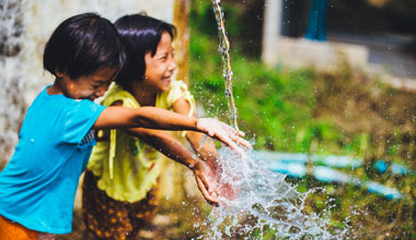 two children playing with clean water