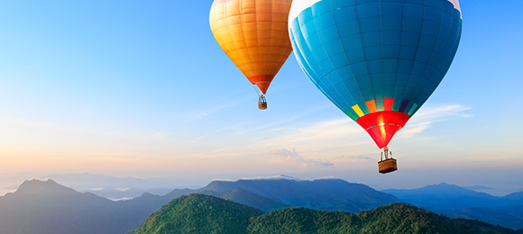 Balloons sailing over mountains