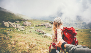 Couple helping each other up a mountain